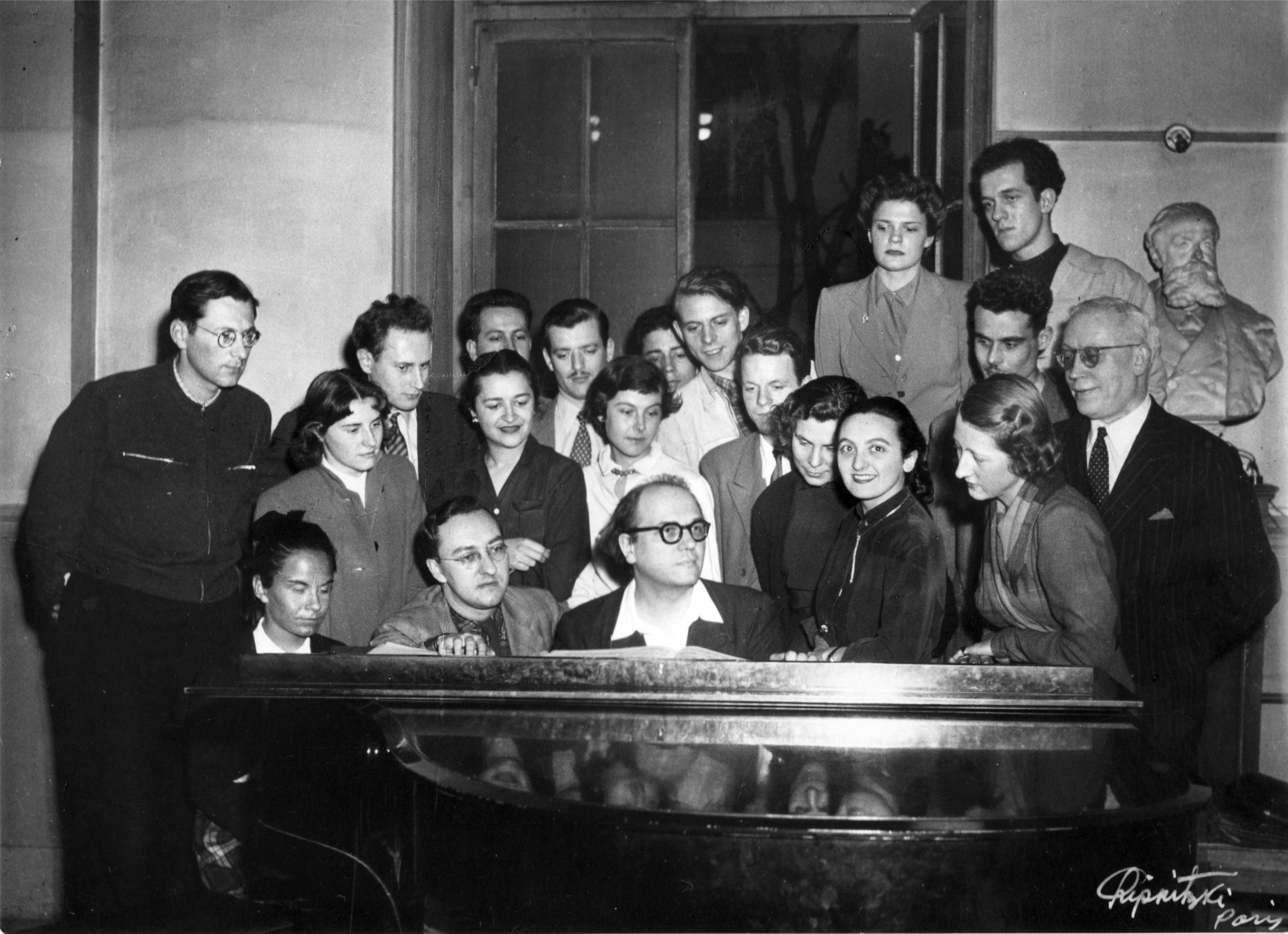 La classe de Messiaen. Je crois reconnaître Stockhausen (penché) au troisième rang…
